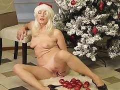Kinky grown-up Sylvie plays with her pussy next to a Christmas tree